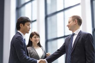 オフィスビルのエントランスで握手をするビジネス男性の写真素材 [FYI02968215]