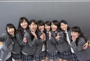 黒板の前に笑顔で並ぶ女子高校生たちのポートレートの写真素材 [FYI02968216]