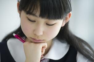 教室でペンを持ち考える女子学生の写真素材 [FYI02968218]