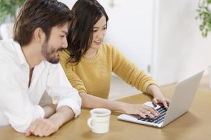 椅子に座ってパソコンを見る男性と女性の写真素材 [FYI02968221]