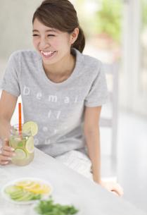 椅子に座ってデトックスウォーターを持って笑う女性の写真素材 [FYI02968224]