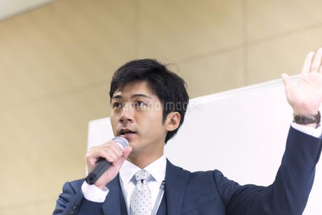 マイクを手に講義するビジネス男性の写真素材 [FYI02968225]