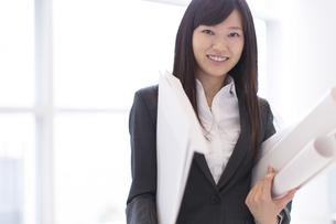 封筒と筒を持って微笑むビジネス女性の写真素材 [FYI02968227]