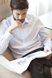 ソファーに座って新聞を読む男性の写真素材 [FYI02968236]