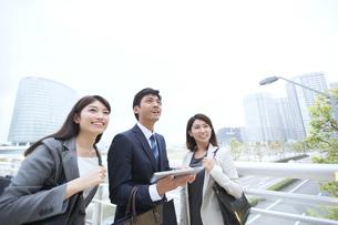街中でタブレットPCを持ち遠くを眺めるビジネス男女の写真素材 [FYI02968240]