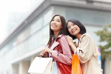 立ち止まって上を向く買い物中の女性二人の写真素材 [FYI02968241]