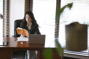 オフィスのデスクで本を読むビジネス女性の写真素材 [FYI02968246]