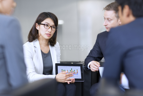 タブレットPCを持ち打ち合せをするビジネス男女の写真素材 [FYI02968248]