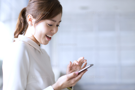スマートフォンを見て笑うビジネス女性の写真素材 [FYI02968250]