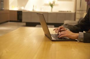 テーブルでノートパソコンを打つ男性の手の写真素材 [FYI02968251]