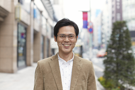 街で微笑む男性のポートレートの写真素材 [FYI02968252]