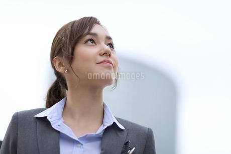 オフィスビルを背景に上を見上げるビジネス女性の写真素材 [FYI02968254]
