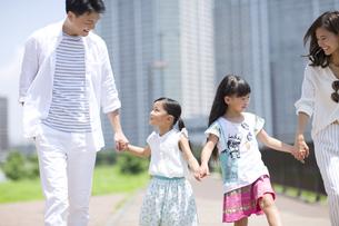 手をつないで遊歩道を歩く家族の写真素材 [FYI02968256]