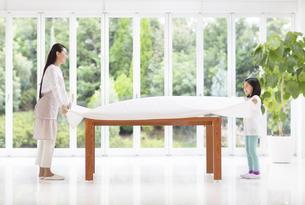 テーブルクロスをかける母と娘の写真素材 [FYI02968258]