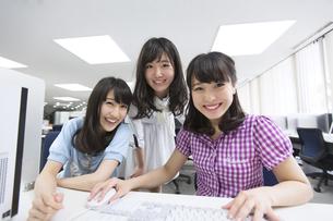 パソコン教室でモニターに向かって微笑む女子学生たちの写真素材 [FYI02968264]