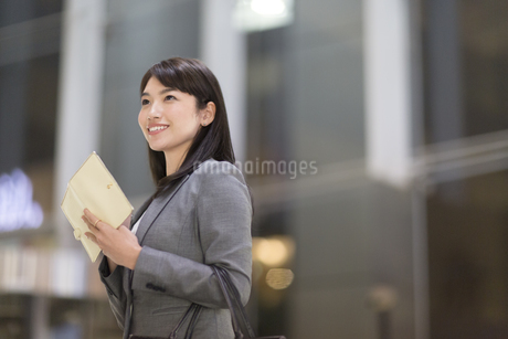 手帳を持ち上を見上げて微笑むビジネス女性の写真素材 [FYI02968267]