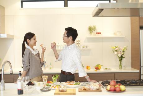 キッチンで食事をつまみ笑い合う夫婦の写真素材 [FYI02968268]