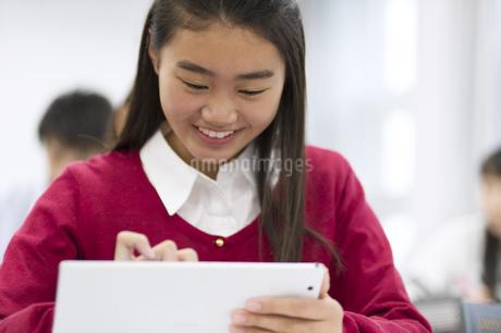 タブレットPCを持って授業を受ける女子生徒の写真素材 [FYI02968269]