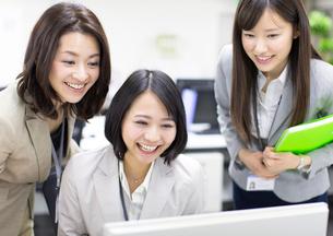 パソコンを見て喜ぶビジネス女性3人の写真素材 [FYI02968274]