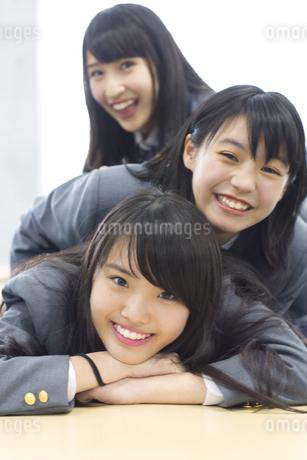 教室の机の上で重なって笑う女子高校生たちの写真素材 [FYI02968276]