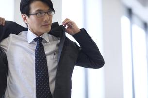 オフィスでスーツのジャケットを羽織るビジネス男性の写真素材 [FYI02968277]