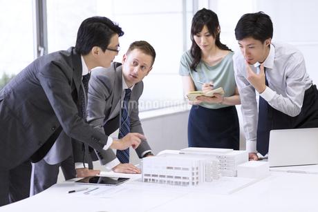会議室で建築模型を使って打ち合せをするビジネス男女の写真素材 [FYI02968278]