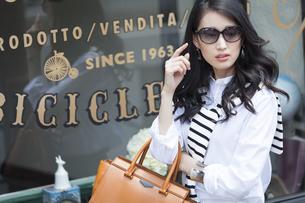 ウィンドウの前でサングラスをかけた女性の写真素材 [FYI02968281]