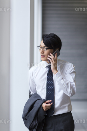 歩きながらスマートフォンで通話するビジネス男性の写真素材 [FYI02968282]