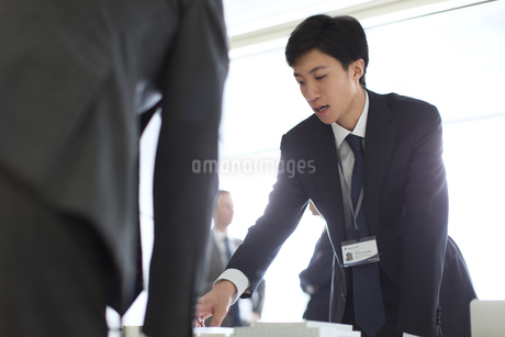 会議室で建築模型を使って打ち合せをするビジネス男性の写真素材 [FYI02968286]