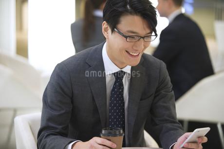オフィスビルのロビーでスマートフォンを見て微笑むビジネス男性の写真素材 [FYI02968291]