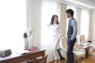 窓際で微笑みながら話す男性と女性の写真素材 [FYI02968292]
