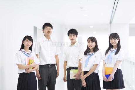 学校の廊下で教材を持って立つ学生たちの写真素材 [FYI02968301]