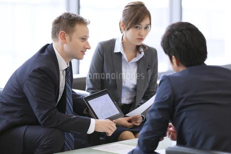 タブレットPCを持ち打ち合せをするビジネス男女の写真素材 [FYI02968303]