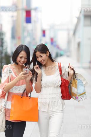 買い物中にスマートホンを見て笑う女性二人の写真素材 [FYI02968305]