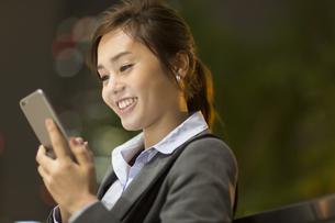 夜の街を背景にスマートフォンを見て笑うビジネス女性の写真素材 [FYI02968307]