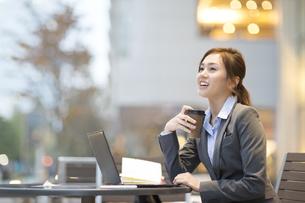 街中でカップを手に持ち上を見上げるビジネス女性の写真素材 [FYI02968319]