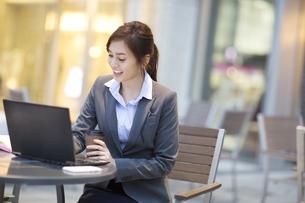 街中でノートPCを操作するビジネス女性の写真素材 [FYI02968320]