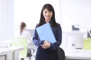 オフィスでファイルを持って微笑むビジネス女性の写真素材 [FYI02968326]