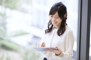 タブレットPCを見て微笑むビジネス女性の写真素材 [FYI02968327]
