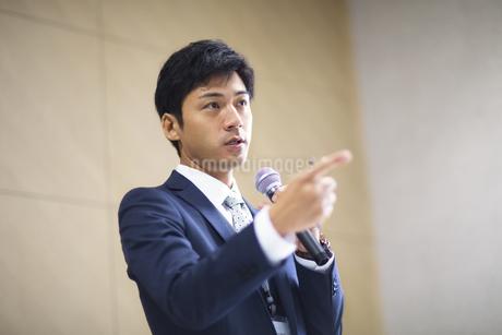 マイクを手に講義するビジネス男性の写真素材 [FYI02968328]