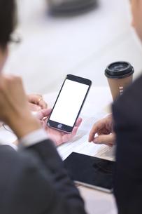 スマートフォンを持ち打ち合せをするビジネス男性の手元の写真素材 [FYI02968331]