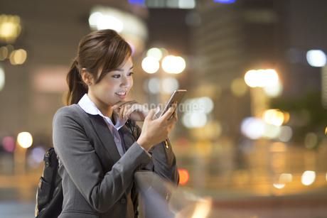 夜の街を背景にスマートフォンを見て微笑むビジネス女性の写真素材 [FYI02968332]