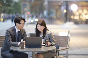 街中で会話しながらノートPCを操作する男女の写真素材 [FYI02968335]