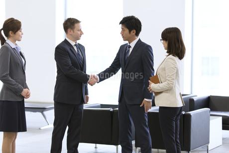 オフィスビルのロビーで握手をするビジネス男性の写真素材 [FYI02968339]