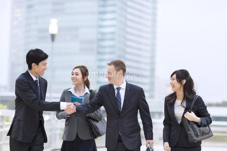 オフィスビルを背景に歩きながら握手を交わすビジネス男女の写真素材 [FYI02968340]