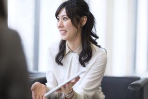 タブレットPCを持ち打ち合せをするビジネス女性の写真素材 [FYI02968343]