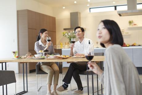 ワインを手に上を見る男女と笑う女性の写真素材 [FYI02968346]