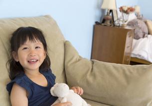 ソファーに座って笑う女の子の写真素材 [FYI02968349]