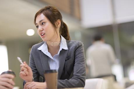オフィスビルのロビーで打ち合せをするビジネス女性の写真素材 [FYI02968350]