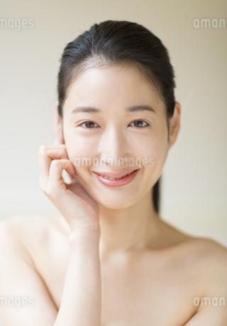頬に片手を添えて微笑む女性の写真素材 [FYI02968351]